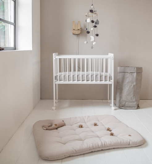 White bedside sleeper crib with baby room interior